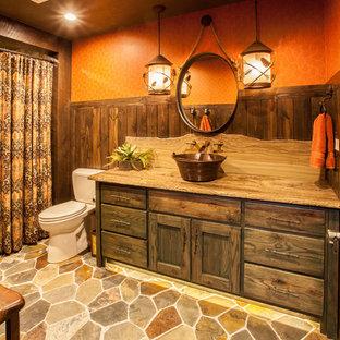 他の地域の中サイズのラスティックスタイルのおしゃれな浴室 (家具調キャビネット、ドロップイン型浴槽、シャワー付き浴槽、分離型トイレ、オレンジの壁、ベッセル式洗面器、珪岩の洗面台、濃色木目調キャビネット) の写真