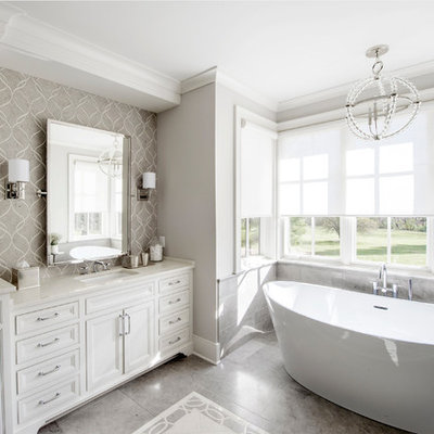 Freestanding bathtub - large traditional master porcelain tile and gray floor freestanding bathtub idea in Columbus with beaded inset cabinets, white cabinets, gray walls, an undermount sink, marble countertops and white countertops
