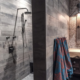 Expansive rustic family bathroom in Calgary with distressed cabinets, a walk-in shower, multi-coloured tiles, pebble tiles, mosaic tile flooring, wooden worktops and shaker cabinets.