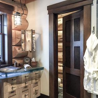 Diseño de cuarto de baño principal, rural, grande, con armarios estilo shaker, puertas de armario de madera oscura, ducha a ras de suelo, baldosas y/o azulejos negros, losas de piedra, suelo de pizarra, lavabo sobreencimera y encimera de vidrio