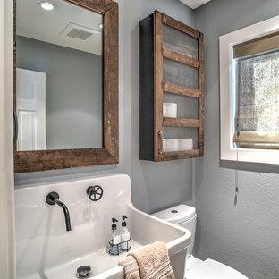 Imagen de cuarto de baño rural, pequeño, con lavabo suspendido, armarios tipo mueble, puertas de armario con efecto envejecido, sanitario de dos piezas, baldosas y/o azulejos de porcelana, paredes grises y suelo de baldosas de porcelana