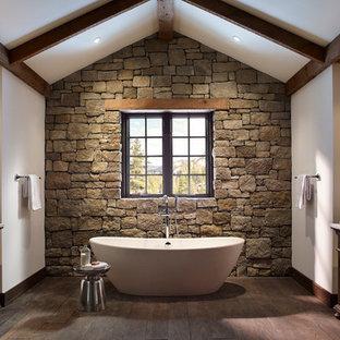 Imagen de cuarto de baño rural, grande, con armarios tipo mueble, puertas de armario de madera en tonos medios, bañera exenta, paredes blancas y suelo de madera oscura