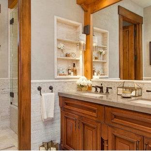 シアトルのラスティックスタイルのおしゃれな浴室 (アンダーカウンター洗面器、レイズドパネル扉のキャビネット、中間色木目調キャビネット、アルコーブ型シャワー、一体型トイレ、ベージュの壁、セラミックタイルの床、ベージュの床) の写真