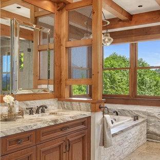Foto de cuarto de baño principal, rural, grande, con lavabo bajoencimera, armarios con paneles con relieve, puertas de armario de madera oscura, bañera encastrada, paredes beige, suelo de baldosas de cerámica, encimera de granito y suelo beige