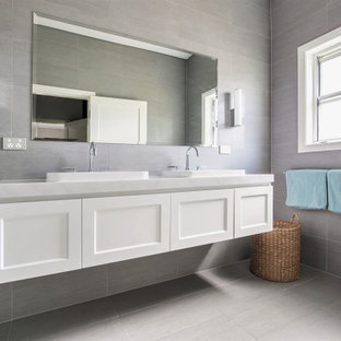 Design ideas for a mid-sized transitional 3/4 bathroom in Sydney with shaker cabinets, white cabinets, an alcove shower, a one-piece toilet, gray tile, limestone, grey walls, porcelain floors, a drop-in sink, marble benchtops, grey floor, a hinged shower door and grey benchtops.