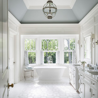 Inspiration for a large beach style master marble floor and white floor bathroom remodel in New York with recessed-panel cabinets, white cabinets, white walls and an undermount sink