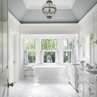 ニューヨークの広いビーチスタイルのおしゃれなマスターバスルーム (落し込みパネル扉のキャビネット、白いキャビネット、大理石の床、白い床、白い壁、アンダーカウンター洗面器) の写真