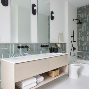 Example of a trendy green tile gray floor and double-sink alcove bathtub design in New York with flat-panel cabinets, light wood cabinets, white walls, a trough sink, white countertops and a floating vanity