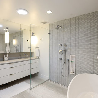 Example of a trendy master gray tile gray floor bathroom design in New York with flat-panel cabinets, white cabinets, white walls, an undermount sink and gray countertops