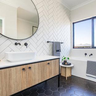 Skandinavisches Badezimmer mit flächenbündigen Schrankfronten, hellen Holzschränken, Eckbadewanne, weißen Fliesen, weißer Wandfarbe, Aufsatzwaschbecken, schwarzem Boden und weißer Waschtischplatte in Melbourne