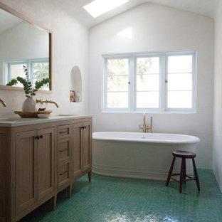 Удачное сочетание для дизайна помещения: главная ванная комната среднего размера в средиземноморском стиле с фасадами с утопленной филенкой, фасадами цвета дерева среднего тона, столешницей из искусственного кварца, белой столешницей, отдельно стоящей ванной, белыми стенами, полом из керамической плитки, врезной раковиной и зеленым полом - самое интересное для вас