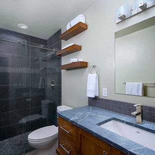 Foto på ett litet industriellt blå badrum, med skåp i shakerstil, skåp i mellenmörkt trä, grå kakel, porslinskakel, grå väggar, klinkergolv i småsten, ett undermonterad handfat, bänkskiva i täljsten, en dusch i en alkov och en toalettstol med separat cisternkåpa
