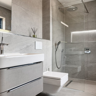 Photo of a medium sized contemporary shower room in Other with flat-panel cabinets, grey cabinets, an alcove shower, a wall mounted toilet, grey tiles, porcelain tiles, porcelain flooring, an integrated sink, grey floors and white worktops.