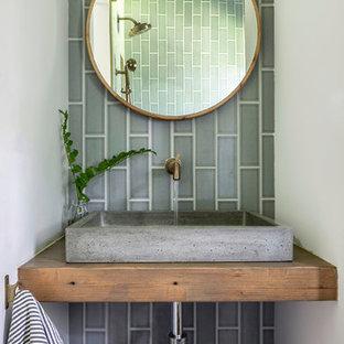 Стильный дизайн: маленькая ванная комната в стиле кантри с открытыми фасадами, искусственно-состаренными фасадами, душем без бортиков, унитазом-моноблоком, синей плиткой, керамической плиткой, белыми стенами, полом из цементной плитки, душевой кабиной, настольной раковиной, столешницей из дерева, серым полом, открытым душем и коричневой столешницей - последний тренд