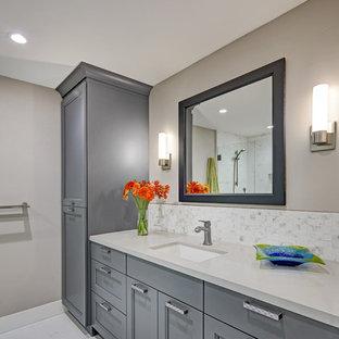 Foto de cuarto de baño tradicional renovado, de tamaño medio, con armarios con paneles empotrados, paredes grises, lavabo bajoencimera, puertas de armario grises, baldosas y/o azulejos blancos y encimeras grises