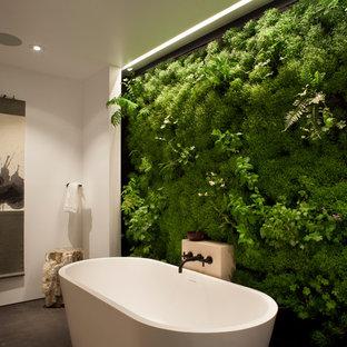 Ispirazione per una stanza da bagno minimal con vasca freestanding e pareti verdi
