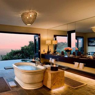 Modelo de cuarto de baño principal, exótico, grande, con bañera exenta, baldosas y/o azulejos amarillos, paredes amarillas, lavabo encastrado, armarios con paneles lisos, puertas de armario negras y suelo gris