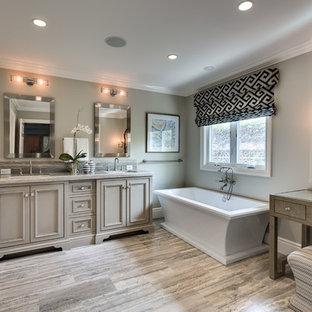 Foto på ett mellanstort vintage en-suite badrum, med luckor med infälld panel, grå skåp, ett fristående badkar, en dusch i en alkov, grå kakel, vita väggar, ljust trägolv, ett undermonterad handfat, marmorkakel, marmorbänkskiva, beiget golv och dusch med gångjärnsdörr