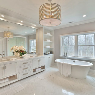 Photo of a classic ensuite bathroom in New York with shaker cabinets, white cabinets, a freestanding bath, beige walls and a submerged sink.