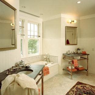 Immagine di una stanza da bagno chic con lavabo sottopiano, vasca da incasso, pareti grigie e top grigio