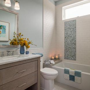 Immagine di una stanza da bagno stile marino con ante in legno scuro, WC monopezzo, piastrelle blu, piastrelle in ceramica, pareti blu, pavimento in gres porcellanato, lavabo sottopiano, top in quarzo composito, pavimento beige, top bianco, ante lisce e vasca ad alcova