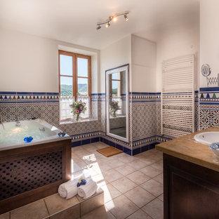 Ispirazione per una stanza da bagno padronale mediterranea di medie dimensioni con ante in legno bruno, vasca idromassaggio, zona vasca/doccia separata, WC a due pezzi, piastrelle beige, piastrelle a mosaico, pareti bianche, lavabo integrato, top in marmo e porta doccia a battente