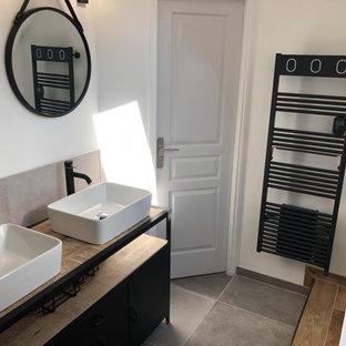 Idee per una stanza da bagno industriale con ante nere, piastrelle grigie, piastrelle di cemento, pareti bianche, pavimento in cementine, top in acciaio inossidabile, pavimento grigio e top nero