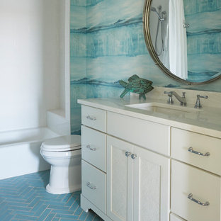 Example of a mid-sized beach style kids' white tile and porcelain tile porcelain tile and turquoise floor bathroom design in Jacksonville with recessed-panel cabinets, white cabinets, a two-piece toilet, blue walls, an undermount sink and marble countertops