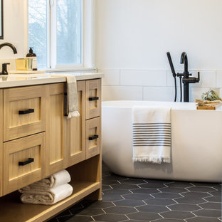 Inspiration for a mid-sized farmhouse master white tile and subway tile porcelain tile and black floor bathroom remodel in Seattle with shaker cabinets, light wood cabinets, a one-piece toilet, white walls, an undermount sink, a hinged shower door, white countertops and quartz countertops