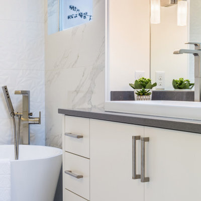 Inspiration for a mid-sized modern master white tile and porcelain tile porcelain tile and white floor bathroom remodel in Seattle with flat-panel cabinets, white cabinets, a one-piece toilet, white walls, a trough sink, quartz countertops, a hinged shower door and gray countertops