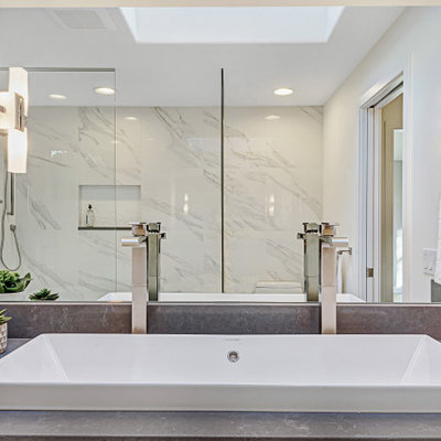 Mid-sized minimalist master white tile and porcelain tile porcelain tile and white floor bathroom photo in Seattle with flat-panel cabinets, white cabinets, a one-piece toilet, white walls, a trough sink, quartz countertops, a hinged shower door and gray countertops