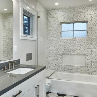 サンフランシスコのトランジショナルスタイルのおしゃれなマスターバスルーム (シェーカースタイル扉のキャビネット、白いキャビネット、アルコーブ型浴槽、シャワー付き浴槽、モノトーンのタイル、白い壁、アンダーカウンター洗面器、珪岩の洗面台、マルチカラーの床、開き戸のシャワー、グレーの洗面カウンター) の写真