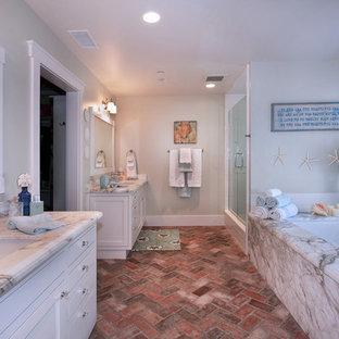 Modelo de cuarto de baño costero con lavabo bajoencimera, armarios con paneles empotrados, puertas de armario blancas, ducha empotrada, suelo de ladrillo, bañera encastrada sin remate y suelo rojo