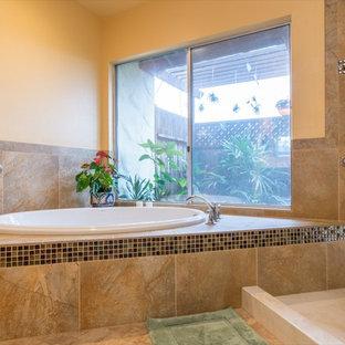 Idee per una grande stanza da bagno padronale tropicale con ante lisce, ante in legno chiaro, vasca da incasso, doccia alcova, piastrelle marroni, piastrelle di vetro, pareti gialle, pavimento in linoleum, lavabo integrato e top in marmo