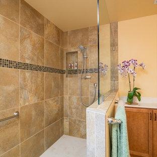 Immagine di una grande stanza da bagno padronale tropicale con ante lisce, ante in legno chiaro, vasca da incasso, doccia alcova, piastrelle marroni, piastrelle di vetro, pareti gialle, pavimento in linoleum, lavabo integrato e top in marmo