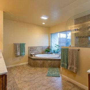 Foto di una grande stanza da bagno padronale tropicale con ante lisce, ante in legno chiaro, vasca da incasso, doccia alcova, piastrelle marroni, piastrelle di vetro, pareti gialle, pavimento in linoleum, lavabo integrato e top in marmo