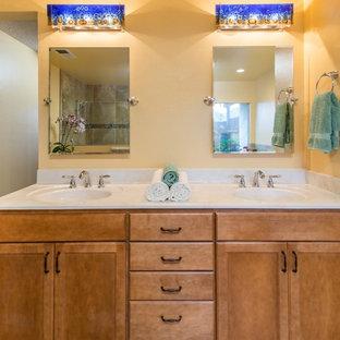 Esempio di una grande stanza da bagno padronale tropicale con ante lisce, ante in legno chiaro, vasca da incasso, doccia alcova, piastrelle marroni, piastrelle di vetro, pareti gialle, pavimento in linoleum, lavabo integrato e top in marmo