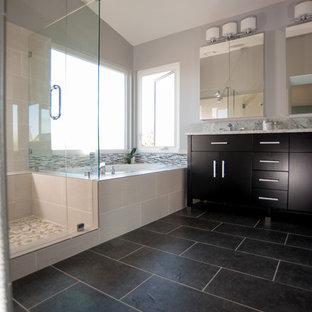 サンディエゴの広いトランジショナルスタイルのおしゃれなマスターバスルーム (フラットパネル扉のキャビネット、濃色木目調キャビネット、ドロップイン型浴槽、コーナー設置型シャワー、分離型トイレ、黒いタイル、セラミックタイル、白い壁、セラミックタイルの床、オーバーカウンターシンク、珪岩の洗面台) の写真