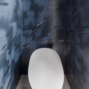 Immagine di una grande stanza da bagno padronale moderna con ante lisce, ante in legno chiaro, vasca sottopiano, doccia ad angolo, pavimento in marmo, lavabo sottopiano, top in quarzo composito, pavimento grigio, porta doccia a battente, WC monopezzo e pareti blu