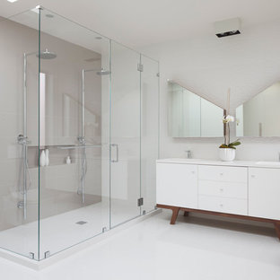 Example of a large trendy master white tile and porcelain tile ceramic floor and beige floor alcove shower design in San Francisco with white cabinets, white walls, flat-panel cabinets, a wall-mount toilet, an integrated sink, engineered quartz countertops, a hinged shower door and white countertops