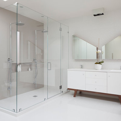 Example of a large trendy master white tile and porcelain tile ceramic tile and beige floor alcove shower design in San Francisco with white cabinets, white walls, flat-panel cabinets, a wall-mount toilet, an integrated sink, quartz countertops, a hinged shower door and white countertops