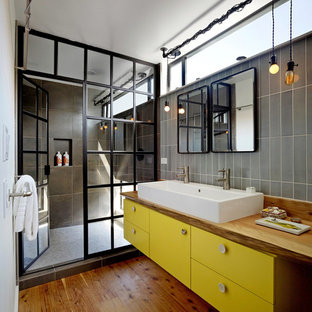 Mid-sized industrial 3/4 bathroom in San Francisco with wood benchtops, flat-panel cabinets, yellow cabinets, an alcove shower, gray tile, porcelain tile, white walls, medium hardwood floors, brown floor, a hinged shower door and brown benchtops.