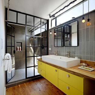 Mittelgroßes Industrial Duschbad mit Waschtisch aus Holz, flächenbündigen Schrankfronten, gelben Schränken, Duschnische, grauen Fliesen, Porzellanfliesen, weißer Wandfarbe, braunem Holzboden, braunem Boden, Falttür-Duschabtrennung und brauner Waschtischplatte in San Francisco