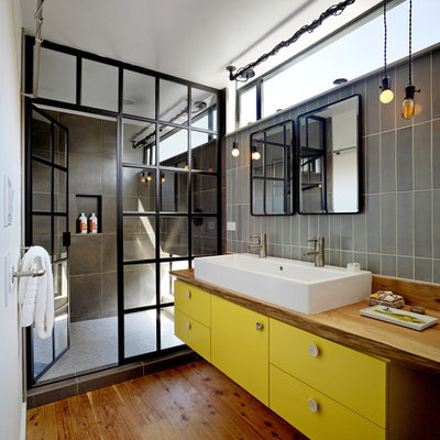 Mid-sized urban 3/4 gray tile and porcelain tile medium tone wood floor and brown floor alcove shower photo in San Francisco with wood countertops, flat-panel cabinets, yellow cabinets, white walls, a hinged shower door and brown countertops