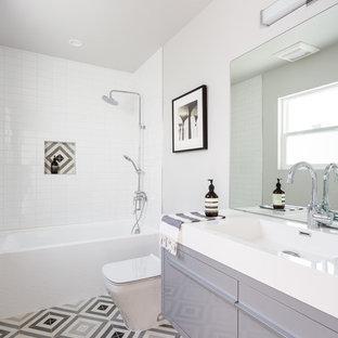 Idéer för mellanstora funkis badrum, med släta luckor, grå skåp, ett badkar i en alkov, en dusch/badkar-kombination, flerfärgad kakel, vit kakel, vita väggar, ett integrerad handfat, flerfärgat golv, cementkakel och cementgolv