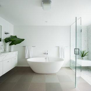 Diseño de cuarto de baño actual con lavabo bajoencimera, armarios con paneles lisos, puertas de armario blancas, bañera exenta, ducha a ras de suelo y baldosas y/o azulejos blancos