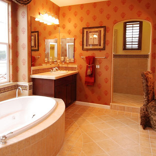Example of a mid-sized tuscan master beige tile and stone tile marble floor bathroom design in Los Angeles with a drop-in sink, raised-panel cabinets, dark wood cabinets, a one-piece toilet and red walls