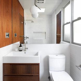 Idéer för ett retro badrum, med släta luckor, skåp i mörkt trä, en toalettstol med separat cisternkåpa, vit kakel, vita väggar, ett konsol handfat och grått golv