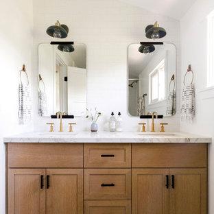 Bild på ett litet vintage vit vitt badrum för barn, med skåp i shakerstil, vit kakel, porslinskakel, vita väggar, cementgolv, ett undermonterad handfat, skåp i mellenmörkt trä och svart golv
