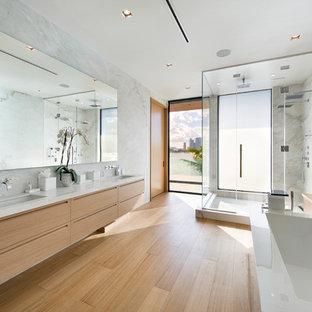 Exempel på ett stort modernt gul gult en-suite badrum, med släta luckor, beige skåp, ett fristående badkar, en dubbeldusch, en vägghängd toalettstol, vit kakel, stenhäll, vita väggar, ljust trägolv, ett undermonterad handfat, marmorbänkskiva, beiget golv och dusch med gångjärnsdörr